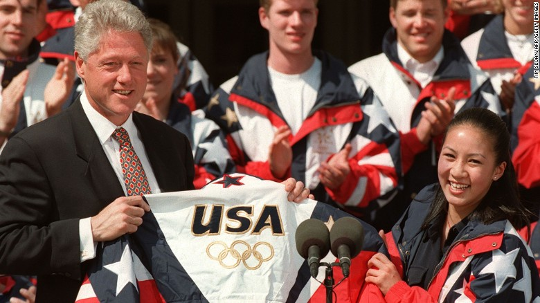 U.S. President Bill Clinton accepts a U.S. Olympic team jacket from U.S. figure skater Michelle Kwan, an Olympic silver medalist 29 April during ceremonies on the South Lawn at the White House in Washington, DC.