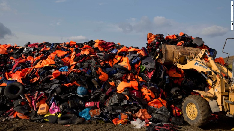 An excavator dumps life vests previously used by migrants on the island of Lesbos, Greece, on Thursday, September 24.