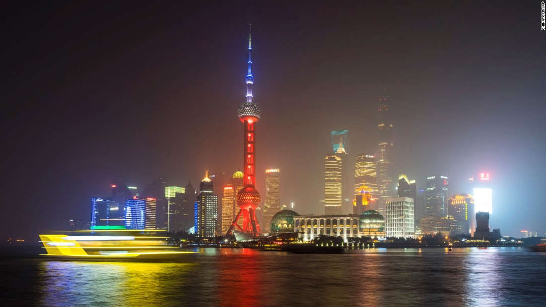 A ferry travels past the Oriental Pearl Tower, lit in the colors of the French flag, in Shanghai, China, on November 14.
