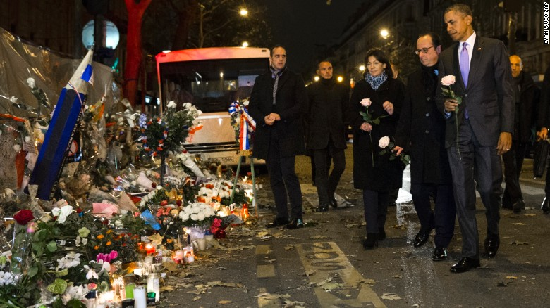 President Barack Obama, French President Francois Hollande, second from right, and Paris Mayor Anne Hidalgo arrive at the Bataclan, site of one of the Paris terrorists attacks, to pay their respects to the victims, on Monday, Nov. 30, 2015, in Paris.