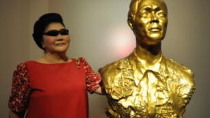 Former first lady Imelda Marcos stands next to a bust of her late husband and Philippine president, Ferdinand Marcos.