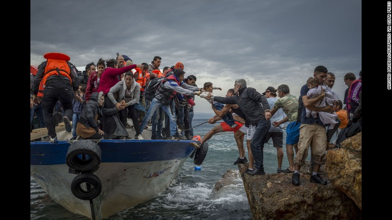 Refugees and migrants get off a fishing boat at the Greek island of Lesbos after crossing the Aegean Sea from Turkey on Sunday, October 11. More than 1 million refugees and migrants escaped to Europe in 2015, the United Nations refugee agency said. Click through to see images from the migration crisis.
