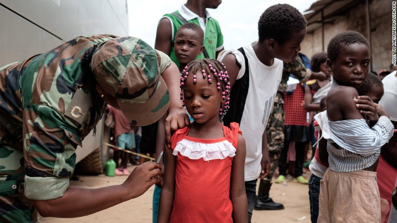 Angolan military administers a yellow fever vaccine to a child at 'Quilometro 30' market, Luanda, Angola.