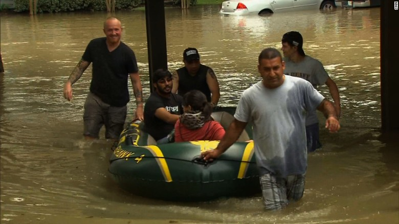 Neighbors pull Ahmed Sharma and his wife, Emily, to safety after floodwater deluged their apartment complex in Klein, Texas.