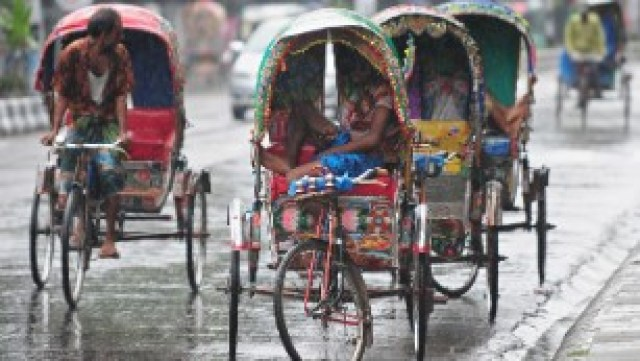 Bangladeshi rickshaw drivers take shelter during a heavy downpour in the capital, Dhaka.