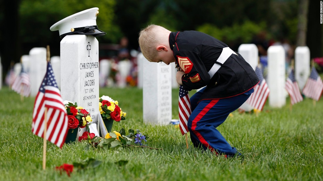 "Christian Jacobs, a 5-year-old from Hertford, North Carolina, puts a flag in front of his father's gravestone at Arlington National Cemetery on Monday, May 30. Marine Sgt. Christopher James Jacobs died in a training accident in 2011. <a href=""http://www.cnn.com/2016/05/28/us/gallery/memorial-day-2016/index.html"" target=""_blank"">See more photos from Memorial Day</a>"