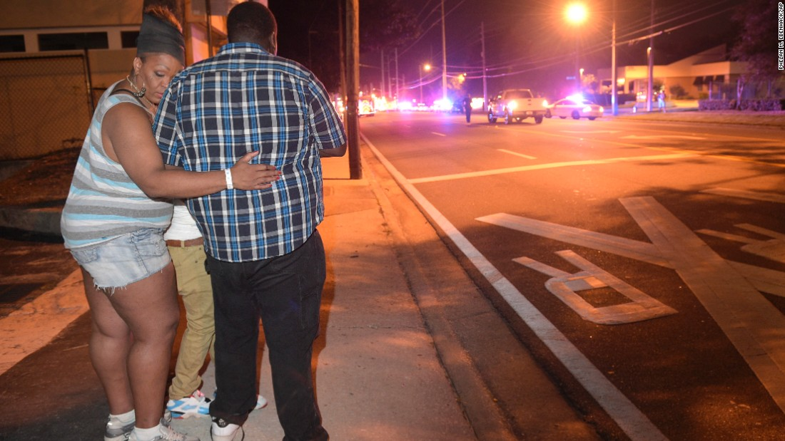 Bystanders wait at the scene.