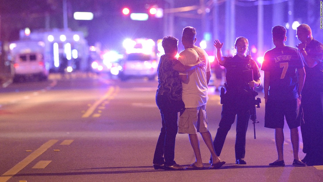 Police in Orlando direct family members away from the scene of the shooting early on June 12.