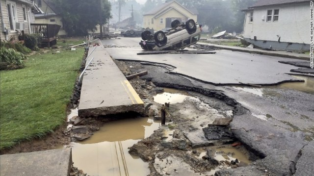 A vehicle rests on its roof after flooding near White Sulphur Springs on June 24.