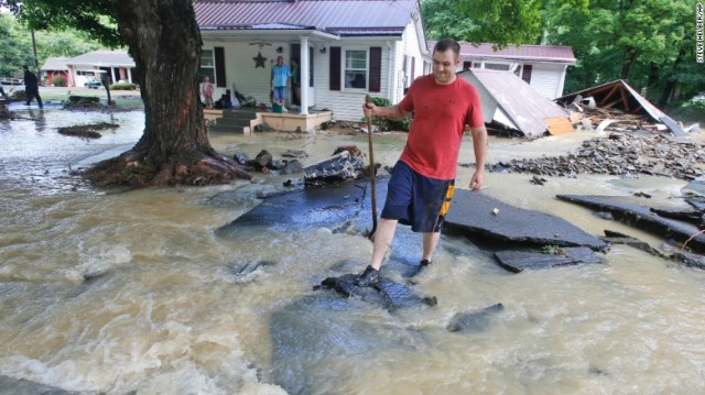 Mark Bowes makes his way to the road after severe flooding in White Sulphur Springs, West Virginia, on Friday, June 24. A state of emergency has been declared in 44 counties.