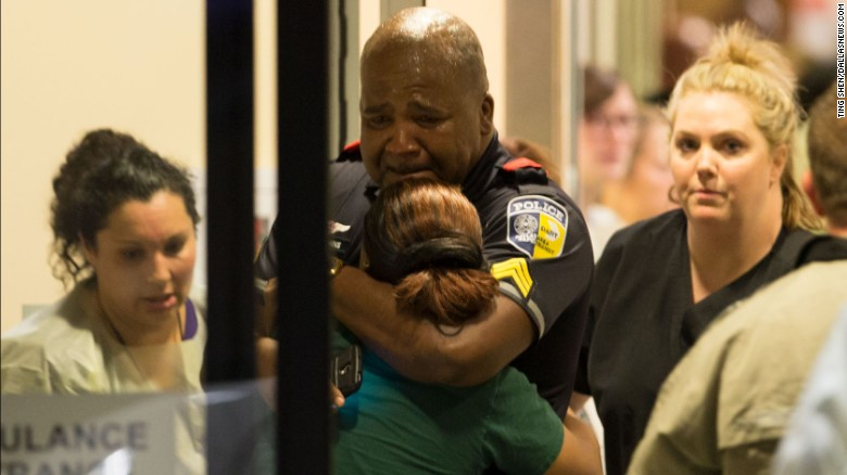 A DART (Dallas Area Rapid Transit) police officer receives comfort at Baylor University Hospital emergency room entrance on July 7, 2016 in Dallas, Texas. Dallas protestors rallied in the aftermath of the killing of Alton Sterling by police officers in Baton Rouge, La. and Philando Castile, who was killed by police less than 48 hours later in Minnesota.  (Ting Shen/The Dallas Morning News) -- MANDATORY CREDIT, NO SALES, MAGS OUT, TV OUT, INTERNET USE BY AP MEMBERS ONLY ORG XMIT: DMN1607072205371652