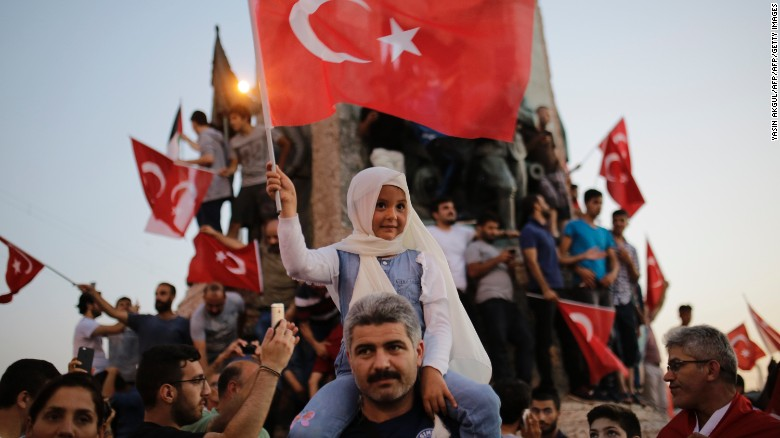 People wave flags in Istanbul's Taksim Square on Saturday in support of  the President.