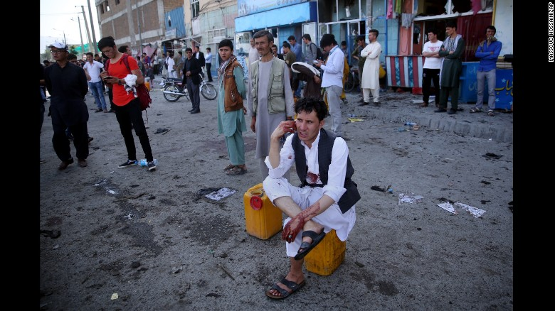 A bloodied man, who carried dead and wounded, speaks on the phone at the site of the suicide attack.