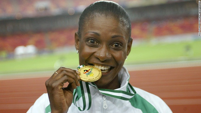 Mary Onyali-Omagbemi bites her gold medal in October, 2003, after receiving her medals at the 8th All African Games in Abuja.