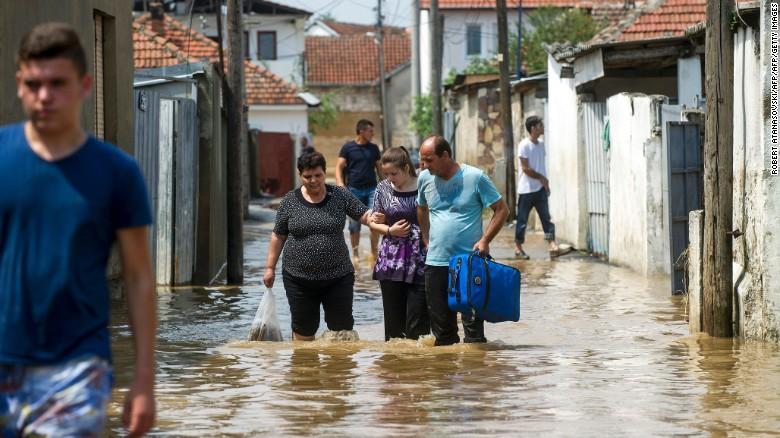 People wade through floodwaters on Sunday in the village of Stajkovci, near Skopje, Macedonia.