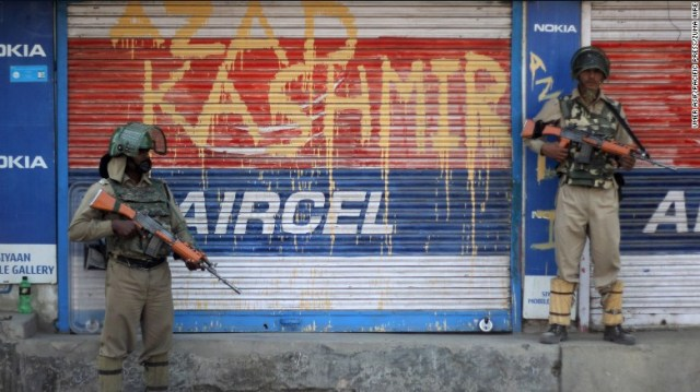 Indian paramilitary troopers stand guard near the graffiti written on shop shutter in Indian-controlled Kashmir.