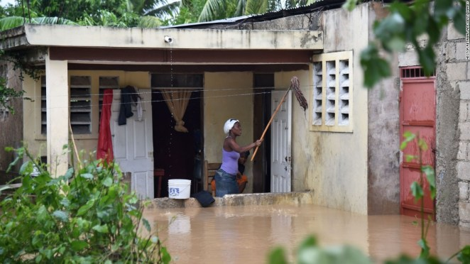 A woman cleans her flooded home after La Rouyonne river overflowed in the commune of Leogane.