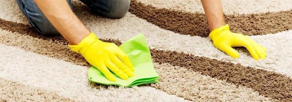 homme nettoyant un tapis a la main