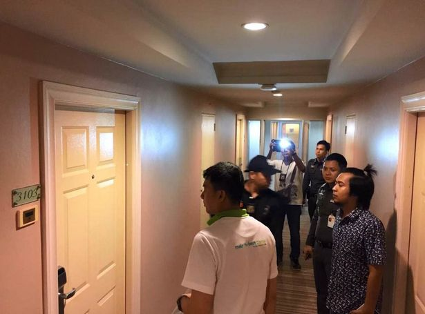 Police officers stand outside the room in Thailand, where the tragedy occurred last week