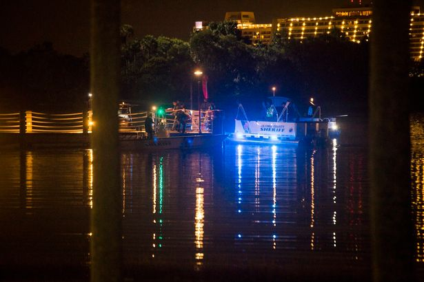 Police officers search for the two-year-old boy after he was dragged into the water by the gator