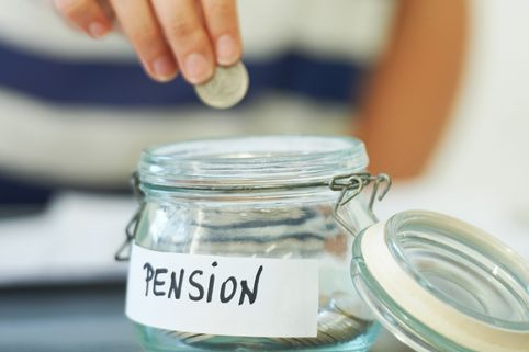A person putting a penny in a jar that is labeled 'Pension'