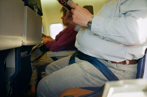A close up of an overweight man's stomach on a plane