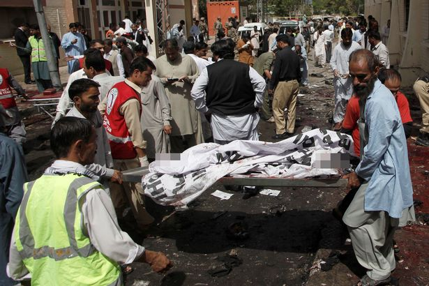 First responders and volunteers transport an injured man away from the scene of a bomb blast outside a hospital in Quetta, Pakistan