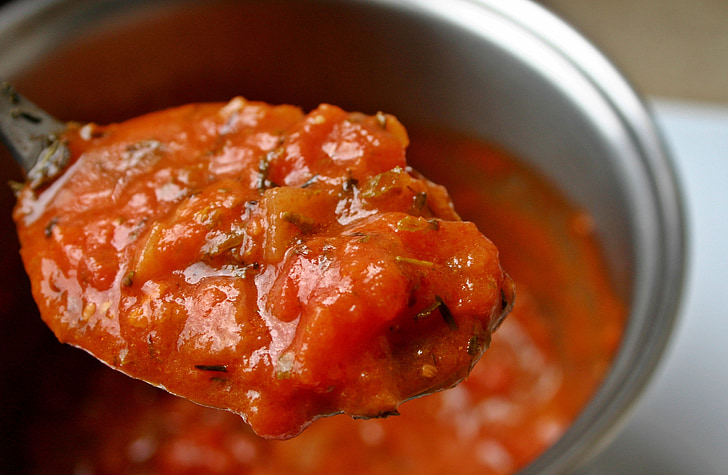 shallow focus photography of red sauce on spoon