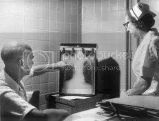 physician and nurse examine a tuberculosis positive chest x-ray