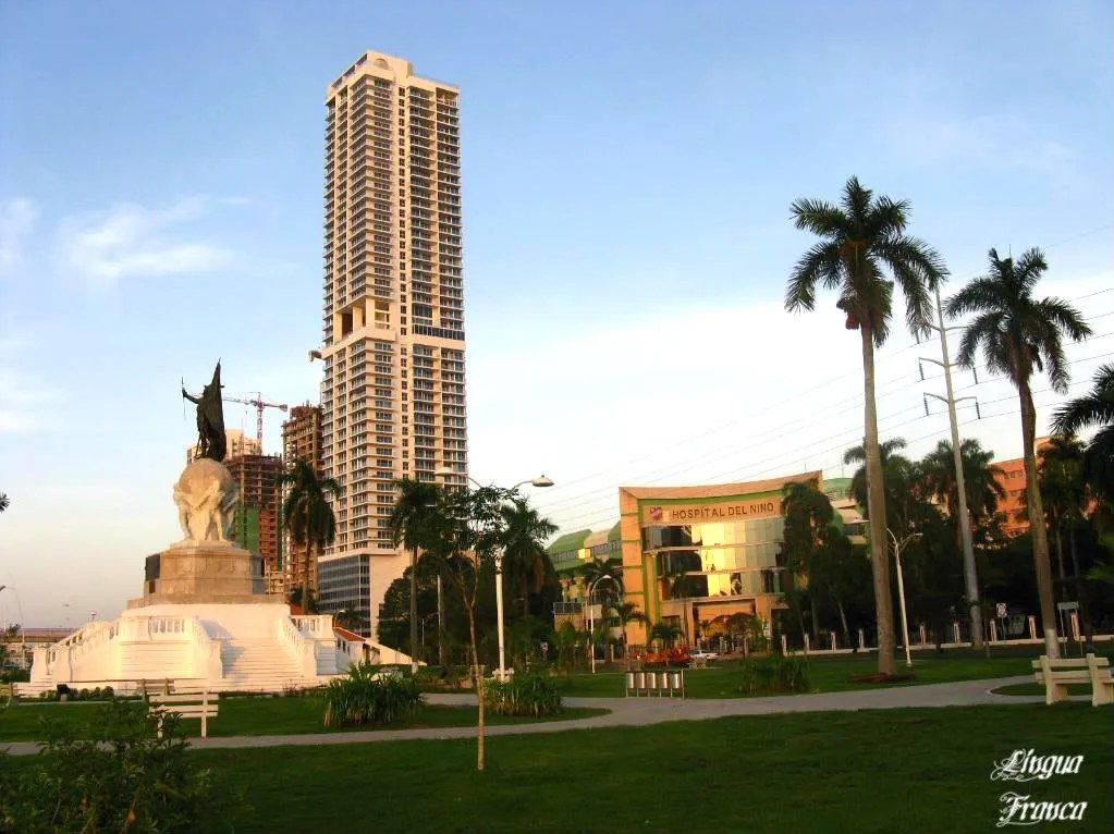 Phototograph of the statue of Vasco Nuñez de Balboa towards your left, almost drowned by the new modern buildings in Panama City, Panama.  (Credit:  Omar Upegui R.)