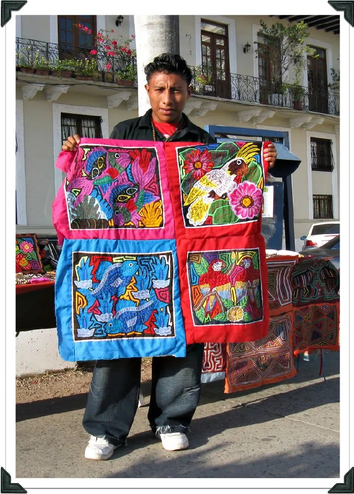 Photograph of a Kuna young man proudly exhibiting four brightly-colored molas.