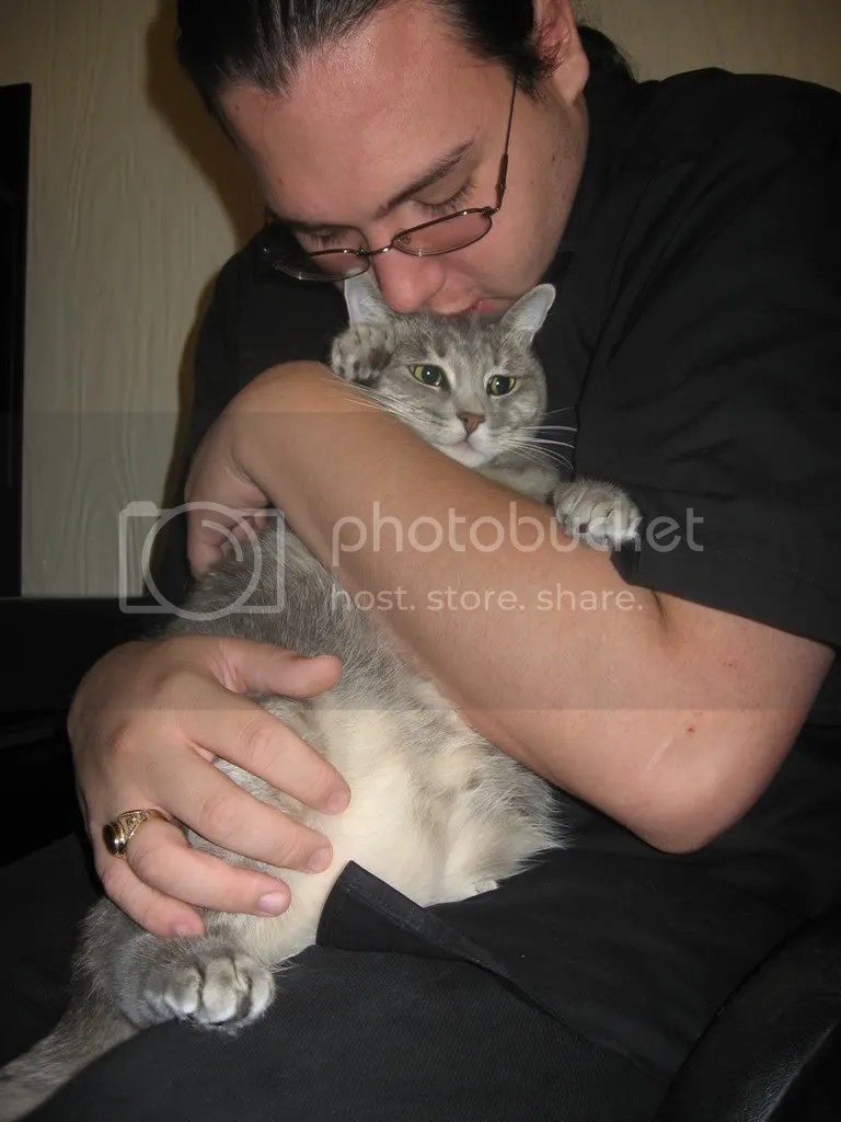 My significant other holding our cat, Monster. Monster looks very embarrassed.