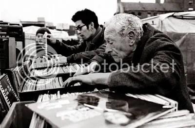 Old man digging through crate of vinyls
