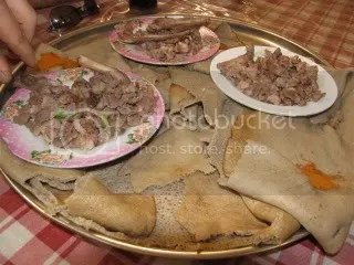 Traditional Ethiopian Food.  Injera is the spongy sheet-like bread, torn onto pieces and used to pick up wat, or piles of meat.  This one is goat, eaten along the way from Addis Ababa to Dire Dawa
