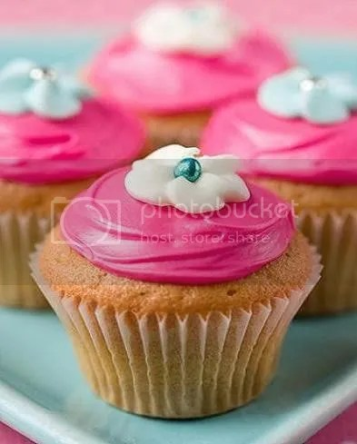 Cupake with pink frosting and a white flower on top