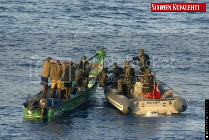 In this photo released by the Turkish military, Turkish commandos are seen with seven pirates in the Gulf of Aden, off Somalia, Saturday, Sept. 26, 2009. The Turkish military said Saturday navy commandos aboard the Turkish frigate TCG Gediz, part of a NATO force patrolling the seas, have captured seven pirates. Commandos raided the skiff, left, Saturday morning upon a request to block it before it could attack a ship. It says a navy helicopter aboard a Turkish frigate also took part in the operation.