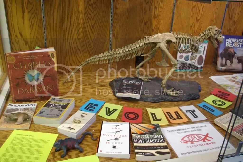 Evolution display with books, a model iguana and a scale model t-rex skeleton