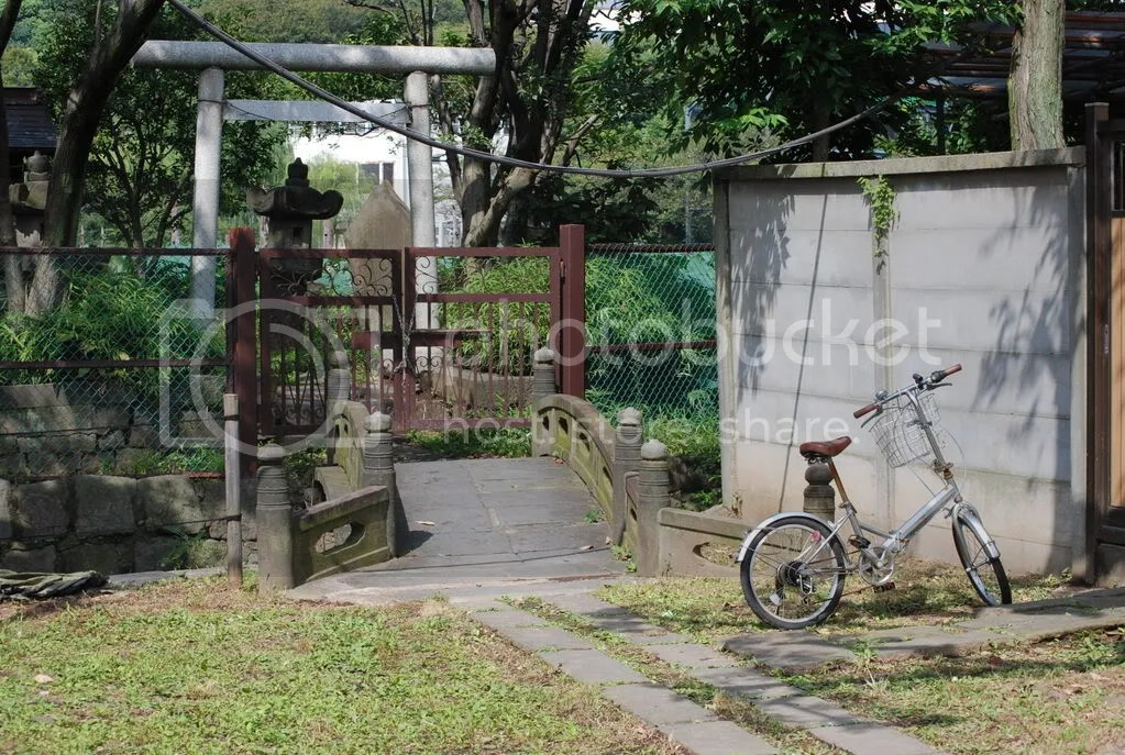 bike parked at the gate to a shrine