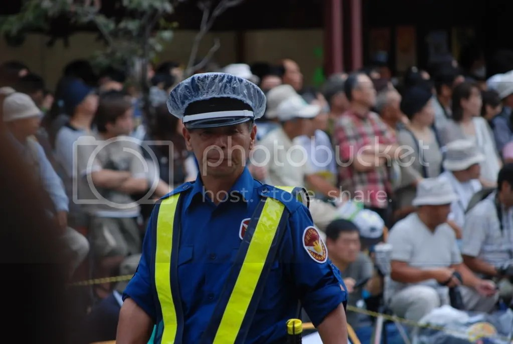 policeman. wearing a plastic bag over his hat in case of rain.