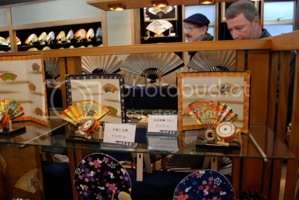 Somemore of the fans for sale, with some tourists checking them out