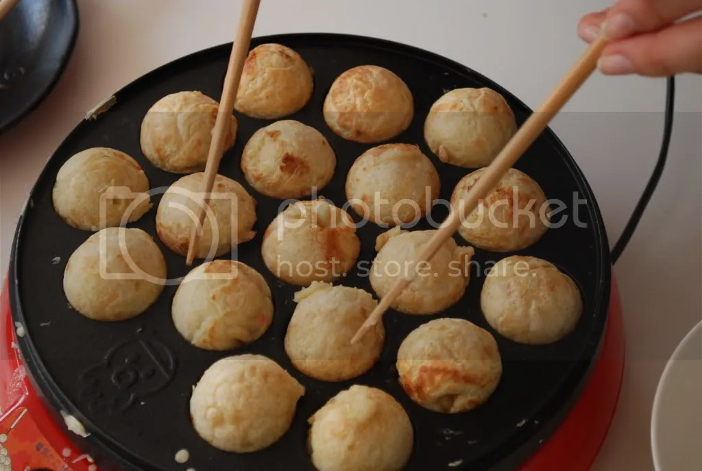 Expertly flipping the takoyaki over to make them into perfect round balls.
