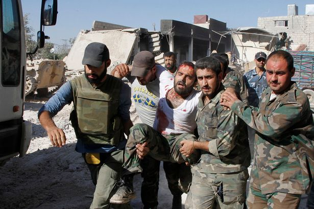 Wounded: Injured Assad soldier is carried away