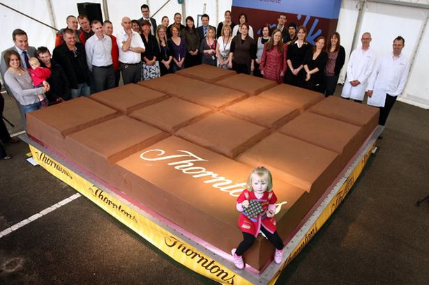 Mia Bell samples some of the world's largest chocolate bar (Pic: PA)