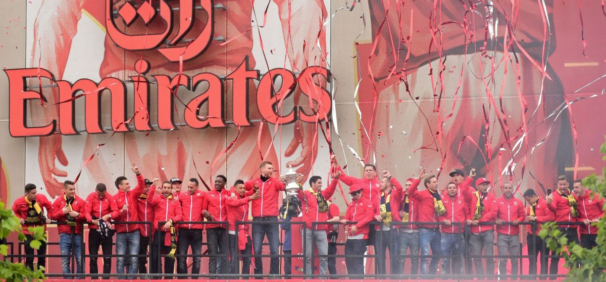 Arsenal players celebrate with the trophy outside Emirates Stadium