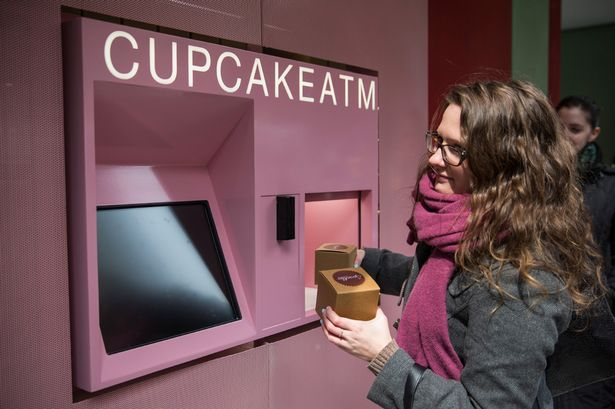 "A woman takes her order of cupcakes after using a ""Cupcake ATM"" created by Sprinkles bakery on March 25, 2014 in New York City"