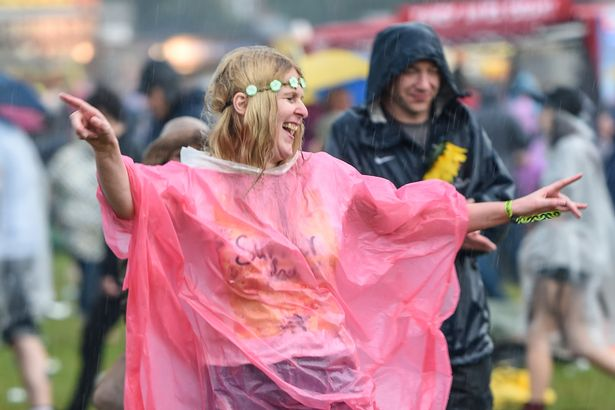 Festival goer wearing rain mac at Isle of Wight Festival