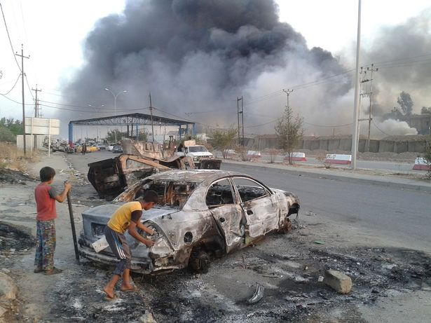 Civilian children stand next to a burnt vehicle during clashes between Iraqi security forces and al Qaeda-linked Islamic State in Iraq and the Levant (ISIL) in Mosul