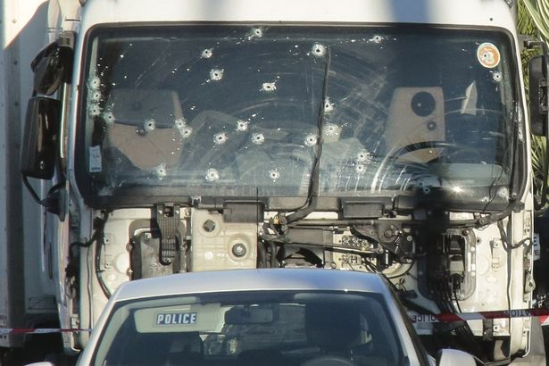 Forensic police investigate a truck at the scene of a terror attack on the Promenade des Anglais