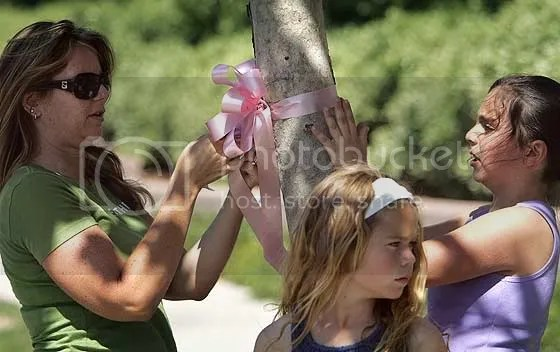Neighbors tie ribbon around tree to honor three children killed in a crash in 2007