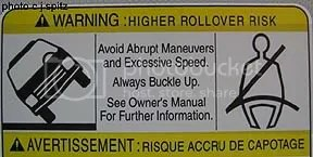 Warning sticker about roll over risk, speed, abrupt manouvers and seatbelts in an SUV